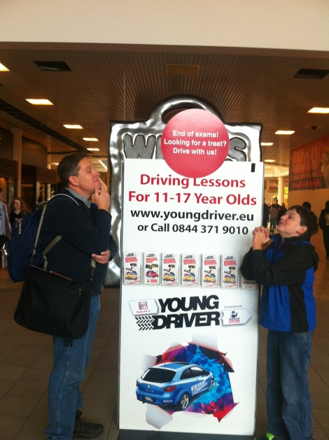 "The sign says, ""Driving lessons for 11-17 year olds.""  Joshua pleads for a chance while his father considers..."